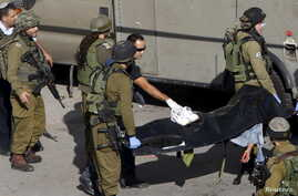 Israeli soldiers carry the body of a Palestinian, who Israeli police and army said was shot by a policeman, after he stabbed a soldier, in the West Bank old city of Hebron, Oct. 29, 2015.