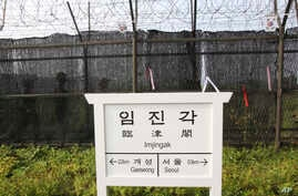 South Korean army soldiers patrol behind a barbed-wire fence near a directional sign showing the distance to North Korea's city Kaesong and South Korea's capital Seoul at the Imjingak Pavilion near the border village of Panmunjom, South Korea, July 5