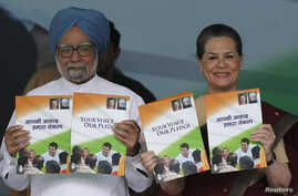 India's Prime Minister Manmohan Singh (L) and Chief of India's ruling Congress party Sonia Gandhi hold their party's manifesto for the April/May general election in New Delhi, March 26, 2014.