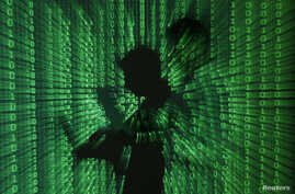 FILE - An illustration picture shows a projection of binary code on a man holding a laptop computer.