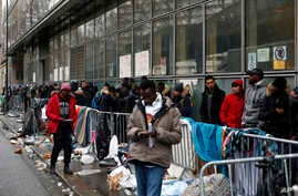 FILE - Migrants queue outside a facility to apply for asylum, in Paris, Dec. 21, 2017.