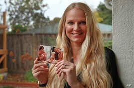 In this  Dec. 5, 2018 photo, Diana Sauer holds a family photograph of her father, Warren Deboer, holding her as a baby, and his best friend Russell Anderson, left, in Concord, Calif.