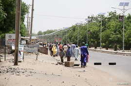 People walk along a road as they flee, in Maiduguri in Borno State, Nigeria May 14, 2015. At least six civilians and six members of a youth vigilante group were killed in an attack by Boko Haram militants on Nigeria's northeastern city Maiduguri, two