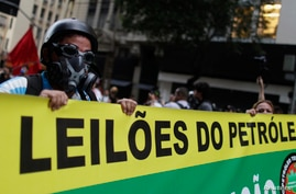 Anti-government demonstrators hold a banner as they walk towards the Petrobras' headquarters, Brazilian state-run energy company, during a protest against the auction for the Libra offshore oilfield, in Rio de Janeiro, Oct. 21, 2013.
