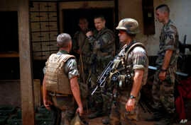 French soldiers search a house used as an armed cache in the Christian sector of PK12, the last checkpoint at the exit of the town, Bangui, Central African Republic, Feb. 11, 2014.