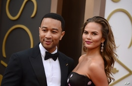 John Legend, left, and Christine Teigen arrive at the Oscars on March 2, 2014, at the Dolby Theatre in Los Angeles.
