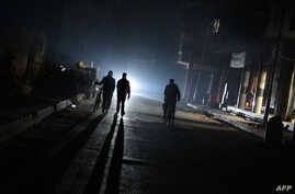 FILE - A group of men walk down a street without electricity late in the besieged rebel bastion of Douma, northeast of the Syrian capital Damascus on Nov. 10, 2014.