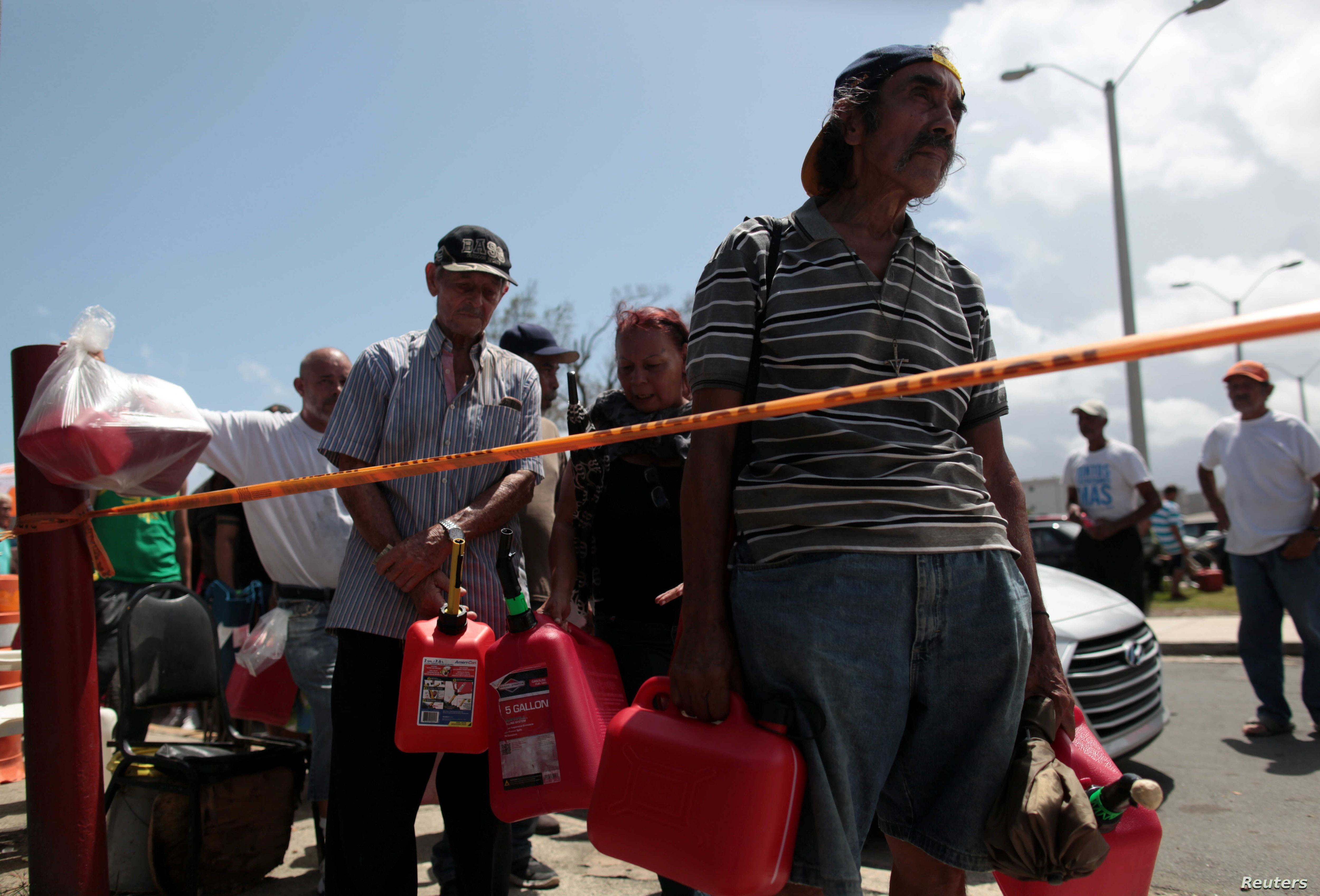 People queue at a gas station to fill up their fuel containers, after the island was hit by Hurricane Maria, in San Juan, Puerto Rico Sept. 28, 2017.
