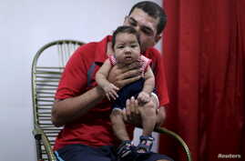 Glecion Fernando holds his 2 month old son Guilherme Soares Amorim, who was born with microcephaly, near at her house in Ipojuca, Brazil, Feb. 1, 2016.