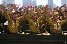 North Korean veterans of the Korean War wave to their leader Kim Jong Un during a mass military parade on Kim Il Sung Square in Pyongyang to mark the 60th anniversary of the Korean War armistice, July 27, 2013