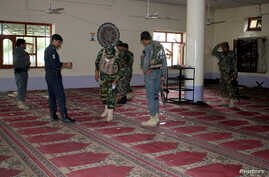Afghan policemen inspect a mosque after a blast in Khost province, Afghanistan, May 6, 2018.