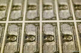 FILE - United States one dollar bills are seen on a light table at the Bureau of Engraving and Printing in Washington, Nov. 14, 2014.