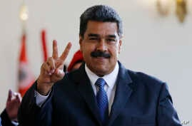 Venezuela's President Nicolas Maduro makes the victory sign after a meeting with former Spanish Prime Minister Jose Luis Rodriguez Zapatero at the presidential palace in Caracas, Venezuela, May 18, 2018. Maduro is seeking a new six-year mandate and,