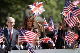 """U.S. First Lady Melania Trump and Philip May, the husband of British Prime Minister Theresa May stand with school children during a visit to British military veterans known as """"Chelsea Pensioners"""" at The Royal Hospital Chelsea in central London Frida"""