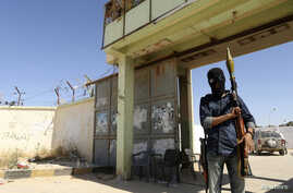 An Islamist fighter guards the entrance to the February 17 militia camp after Libyan irregulars clashed with them in the eastern city of Benghazi, May 16, 2014.