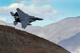 FILE - An F-15E Strike Eagle from Seymour Johnson AFB in North Carolina flies out of the nicknamed Star Wars Canyon turning toward the Panamint range over Death Valley National Park, California, Feb. 27, 2017.