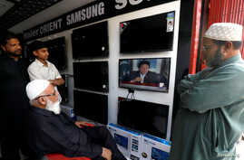 Shopkeepers watch the speech of Pakistani Prime Minister Imran Khan, after Pakistan shot down two Indian military aircrafts, at a shop selling television screens in Karachi, Pakistan, Feb. 27, 2019.