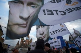 People rally in support of Crimea joining Russia, with banners and portraits of Russian President Vladimir Putin, reading 'We are Together,' in Red Square in Moscow, Tuesday, March 18, 2014.