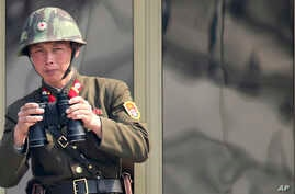 A North Korean soldier watches the South Korean side at the border village of Panmunjom in the demilitarized zone (DMZ) in South Korea, April 4, 2013.