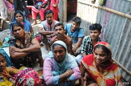 Volunteers in a slum in Dhaka listen to a lecture on reproductive health. (Amy Yee for VOA News)