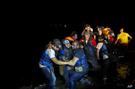 Two Syrian refugees try to carry an elderly woman off a dinghy as it arrives from the Turkish coast to the northeastern Greek island of Lesbos, Oct. 6 , 2015.
