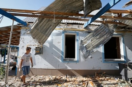 A man walks past a house damaged by recent shelling on the outskirts of the southern coastal town of Mariupol, Ukraine, Sept. 7, 2014.