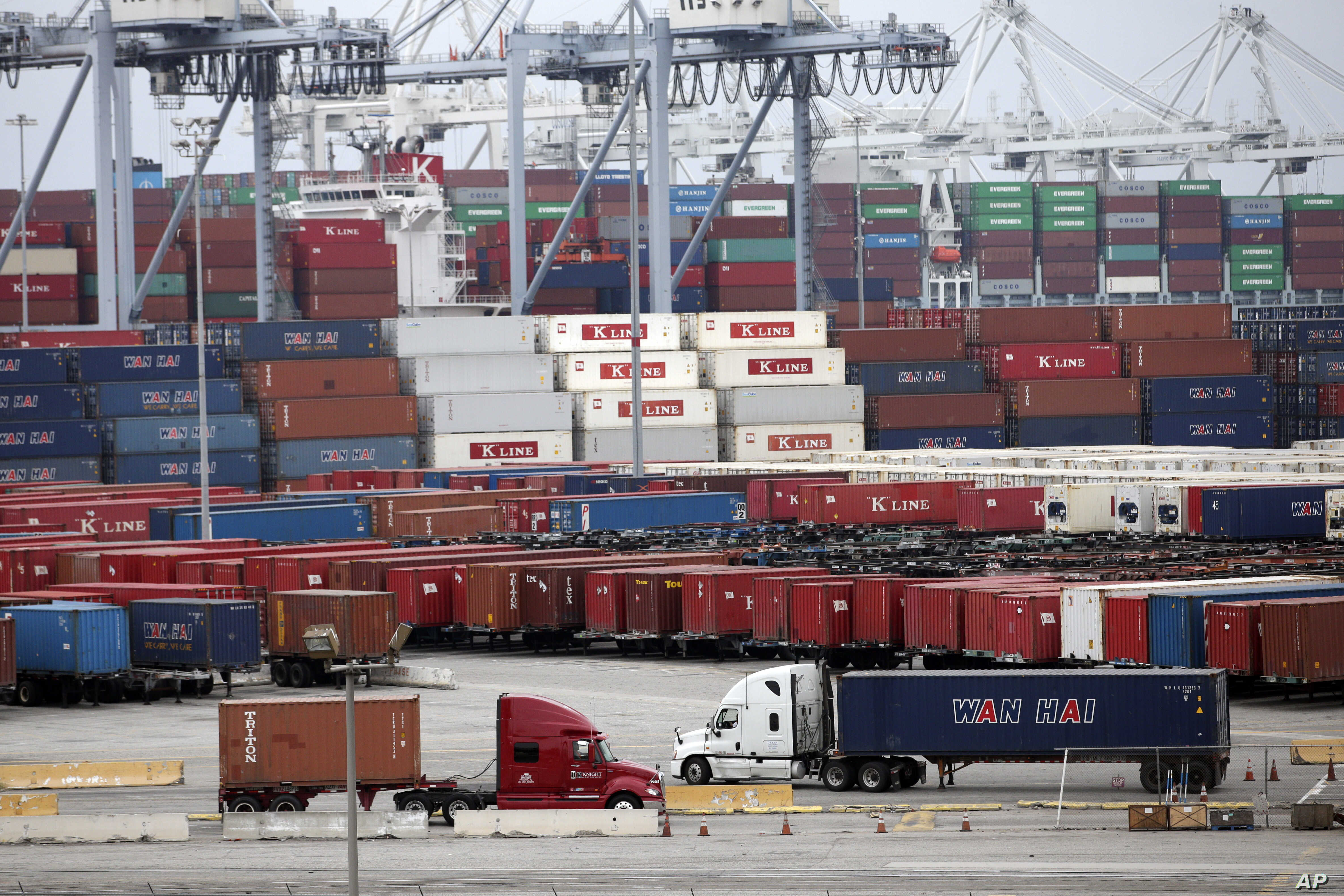 Two trucks move shipping containers at the Port of Long Beach, Feb. 17, 2015, in Long Beach, California.