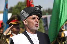"""Afghan President Ashraf Ghani sings the national anthem after putting flowers on the """"Independence Minaret"""" monument during Independence Day celebrations at Defense Ministry in Kabul, Aug. 18, 2016."""