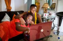 FILE - Yaisah Val, 46, a transgender woman, watches a movie with her husband, Richecarde Val, 28, in their home in Port-au-Prince, Haiti, on July 14, 2018.