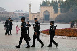 FILE - Uighur security personnel patrol near the Id Kah Mosque in Kashgar in western China's Xinjiang region, Nov. 4, 2017.
