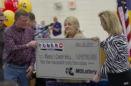 Mark, left, and Cindy, center, Hill are presented a check by a Missouri Lottery official during the announcement of Powerball winners in Dearborn, Missouri, November 30, 2012.