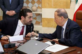 In this photo released by the Lebanese Government, Lebanese President Michel Aoun, right, speaks with Prime Minister Saad Hariri, at the Presidential Palace in Baabda, east of Beirut, Lebanon, Dec. 5, 2017.