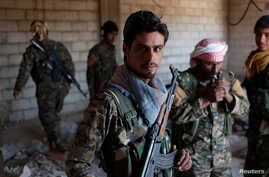 Kurdish fighters from the People's Protection Units (YPG) stand in a house in Raqqa, Syria, June 21, 2017.