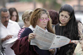 Voters read the a sample ballot as they wait in line to cast their vote in Hialeah, Florida, November 6, 2012.