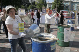 FILE - Protesters, critical of the government's handling of the economy, are seen banging on empty barrels as they rally in downtown in Kyiv, Ukraine, May 21. 2015.