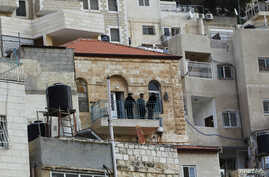 Israeli guards stand on the balcony of a house purchased by Jews in the mostly Arab neighborhood of Silwan in east Jerusalem, Oct. 20, 2014.