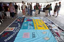 People gather around a section of the AIDS Memorial Quilt, on the National Mall in Washington, July 21, 2012.