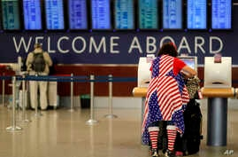 Judy Izzie, dressed in the theme of the American flag, checks in for her flight at Hartsfield-Jackson Atlanta International Airport ahead of the Thanksgiving holiday in Atlanta, Wednesday, Nov. 22, 2017.