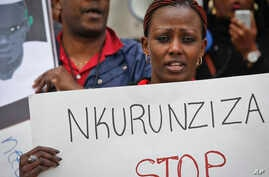 A protester holds up a poster as Burundi nationals from across the U.S. and Canada, along with supporters, demonstrate outside U.N. headquarters, calling for an end to atrocities and human rights violations in Burundi under the government of Presiden...