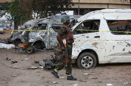 A soldier walks past damaged buses following an explosion at a bus park in Abuja, Nigeria,  April. 14, 2014.
