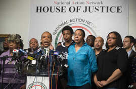 Rev. Al Sharpton speaks alongside Gwen Carr, mother of Eric Garner, left, Esaw Garner, Garner's wife, center right, and Emerald Garner, Garner's daughter, second from right, at the National Action Network headquarters in New York on Wednesday, Dec. 3