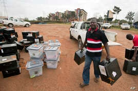 An electoral worker delivers boxes to a district counting center in Kampala, Uganda, Feb. 20, 2016.