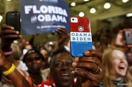 A supporter uses her personalized mobile phone to take a picture of U.S. President Barack Obama as he speaks at a campaign event at the Florida Institute of Technology in Melbourne, Florida, September 9, 2012