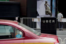 A taxi passes by an Uber station outside a shopping mall in Beijing on August 1, 2016.