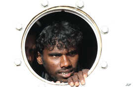 A Sri Lankan asylum seeker who was rescued from a troubled boat adrift trying to reach Australia looks out from a porthole of a rescue ship upon arrival at Teluk Bayur port in Padang, West Sumatra, Indonesia, January 2, 2013.