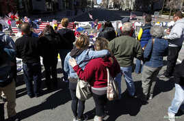 Sarah Orr (L) hugs her sister Heather (R) at a memorial to the victims of the Boston Marathon bombings near the scene of the blasts on Boylston Street in Boston, Massachusetts, Apr. 21, 2013.
