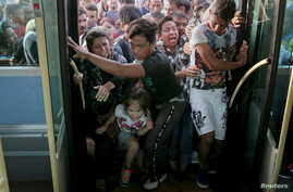 Refugees and migrants push each other as they try to board a bus following their arrival onboard the Eleftherios Venizelos passenger ship at the port of Piraeus, near Athens, Greece, Sept. 7, 2015.