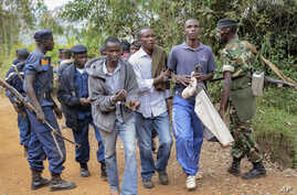 FILE - Three men walk in handcuffs after being arrested as organizers of an opposition demonstration, which was dispersed by police firing in the air, in Jenda, Burundi, June 12, 2015.