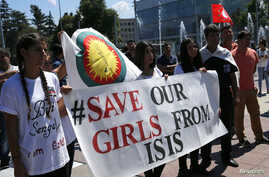 FILE - Women hold a banner during a demonstration marking the first anniversary of Islamic State's surge on Yazidis of the town of Sinjar, in front of the United Nations European headquarters in Geneva, Switzerland, August 3, 2015.