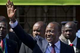 Kenya's President-Elect Uhuru Kenyatta gestures to supporters as he leaves the National Election Center where final election results were announced declaring he would be the country's next president, in Nairobi, Kenya Saturday, March 9, 2013. Uhuru K